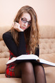 Young woman wearing glasses reading thick book on a sofa - PhotoDune Item for Sale