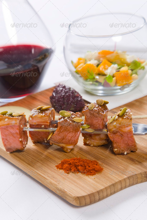 Beef served on skewers with condiments and red wine - Stock Photo - Images