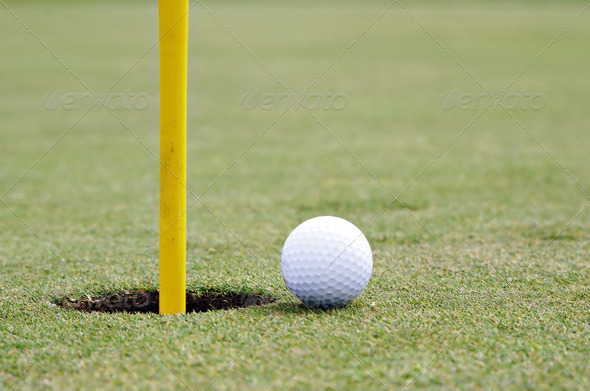 golf ball on the edge of the cup - Stock Photo - Images