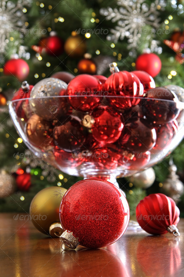 Christmas ornaments on table in front of tree - Stock Photo - Images