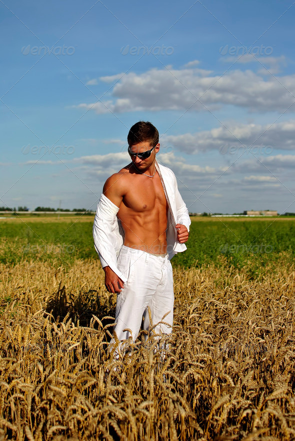Bodybuilder dressed in white on the field - Stock Photo - Images