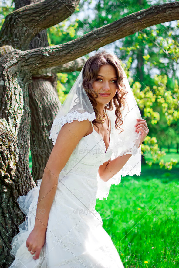 Attractive Bride stands about trees in the park - Stock Photo - Images