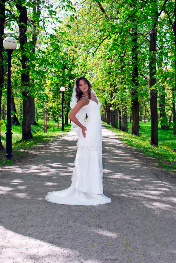 young bride standing in an alley in the park - Stock Photo - Images