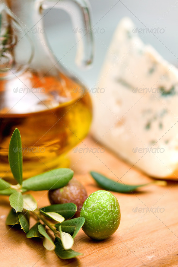 bottle of olive oil on old wooden table and cheese - Stock Photo - Images