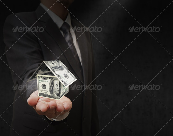 Businessman hand holds a dollar house - Stock Photo - Images