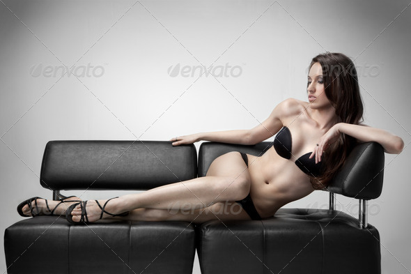sexy woman in swimsuit lies on the sofa - Stock Photo - Images