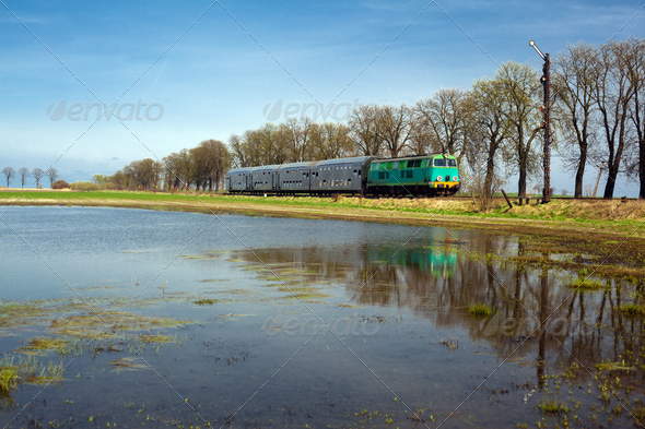 Passenger train passing through countryside - Stock Photo - Images