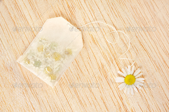 Tea bag - bag of chamomile tea over wooden background - concept - Stock Photo - Images
