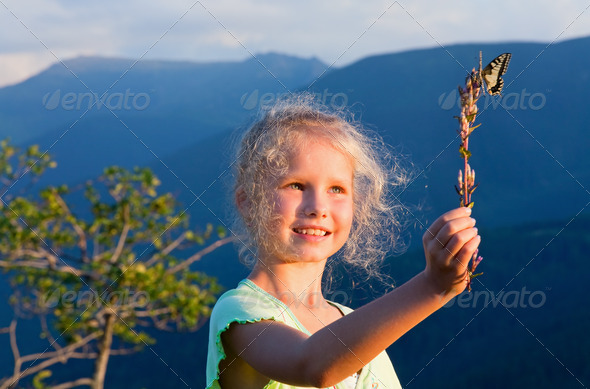 Girl and butterfly in sunset mountain - Stock Photo - Images