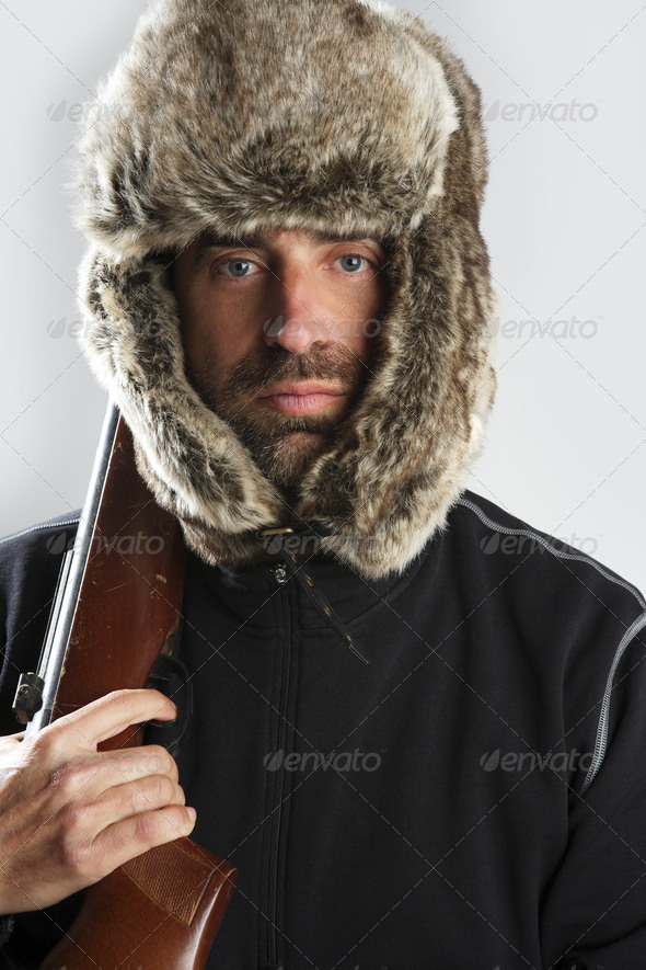 hunter winter fur hat man portrait holding gun - Stock Photo - Images