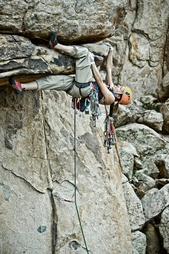 Rock climber clinging to a steep cliff. - Stock Photo - Images