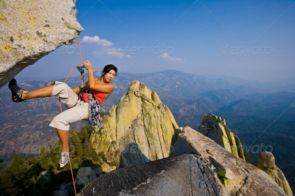 Female rock climber rappelling. - Stock Photo - Images