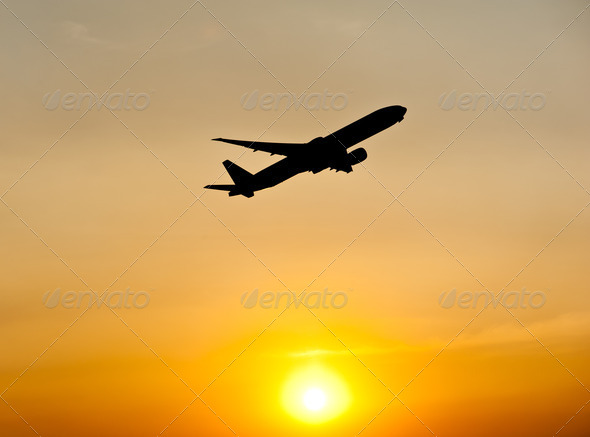 Airplane silhouette over sunset  - Stock Photo - Images