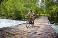 Mountain biker goes on old wooden bridge - PhotoDune Item for Sale