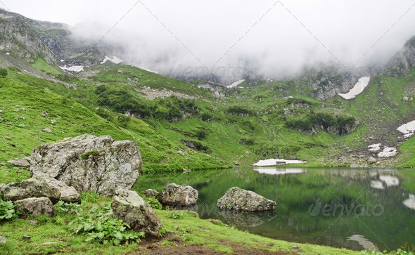 Stones on mountain lake with reflection - Stock Photo - Images