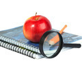 Magnifying glass, pencil and red apple on spiral notebooks - PhotoDune Item for Sale
