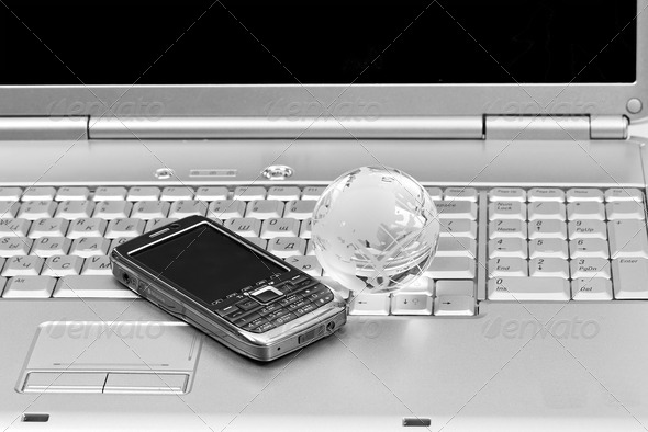 Mobile phone and glass globe on laptop keyboard. Black & White i - Stock Photo - Images