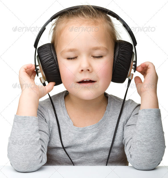 Cute girl enjoying music using headphones - Stock Photo - Images