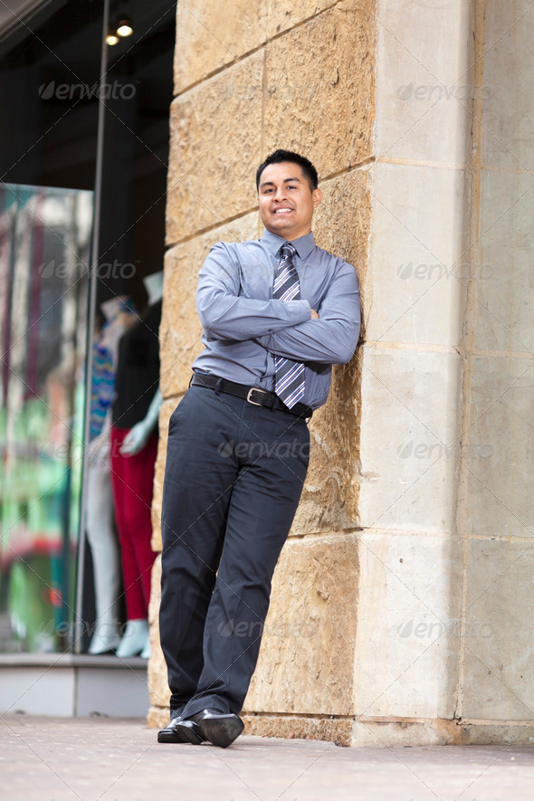 Hispanic Businessman - Leaning on stone wall - Stock Photo - Images