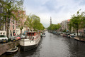 Typical Amsterdam's canal with and boats parked along it - PhotoDune Item for Sale
