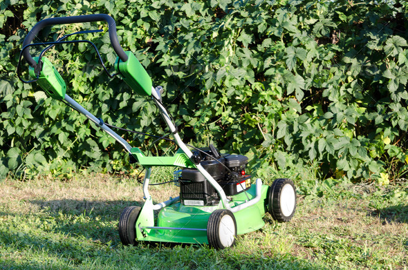 Lawn mower against grass - Stock Photo - Images