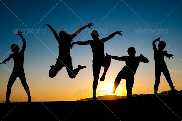 happy kids silhouettes jumping on  the beach - Stock Photo - Images