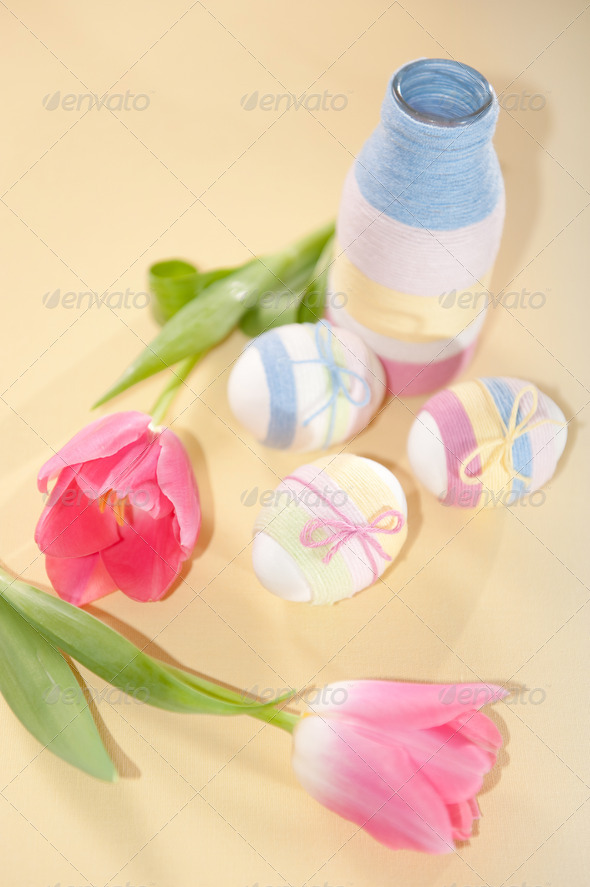 Pink tulips, Easter eggs and yarn wrapped bottle - Stock Photo - Images