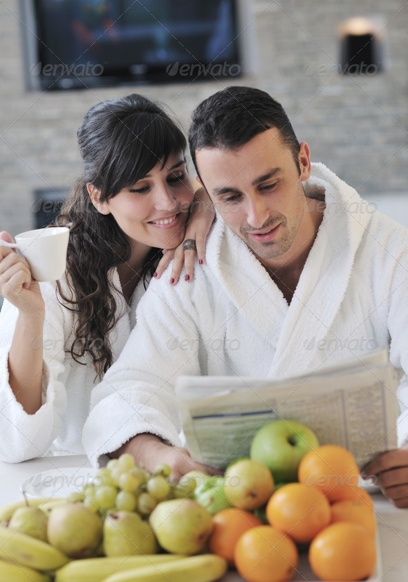Happy couple reading the newspaper in the kitchen at breakfast - Stock Photo - Images