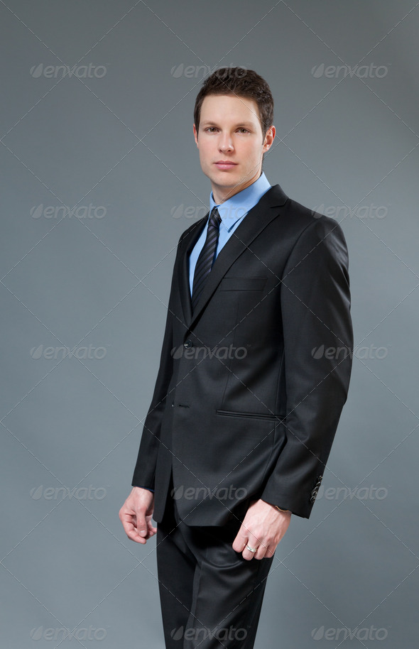 Young businessman wearing classic dark suit. Half-turn studio shot. One of a series. - Stock Photo - Images