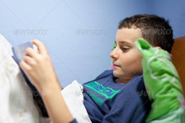 Kid reading a book at bedtime - Stock Photo - Images
