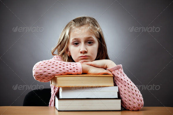 Unhappy schoolgirl with a stack of books - Stock Photo - Images