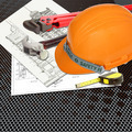 Orange Helmet of relate or rescue constructor with blueprints building construction and tools - PhotoDune Item for Sale