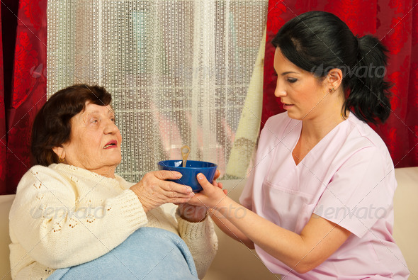Nurse giving bowl with soup to senior - Stock Photo - Images