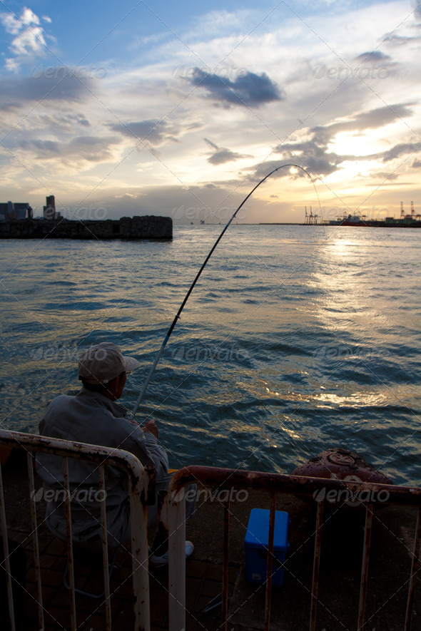 Man fishing during sunset - Stock Photo - Images