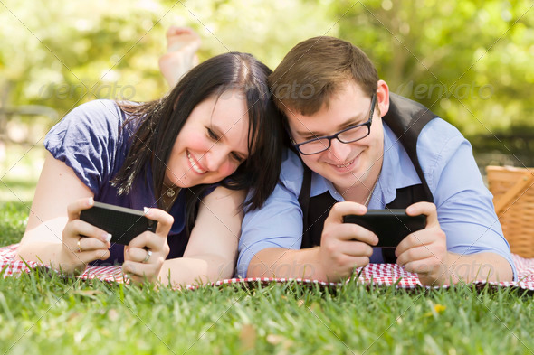 Attractive Young Couple at the Park Texting on Their Smart Phones Together. - Stock Photo - Images
