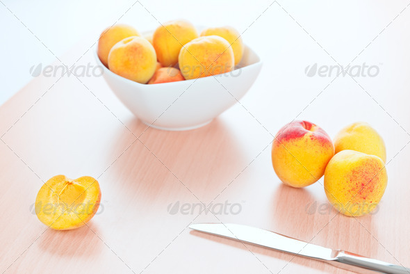 Fresh Apricots and a table knife on kitchen wooden background - Stock Photo - Images