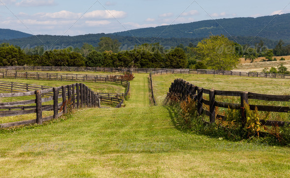 Rolling meadows with wooden fences and hills - Stock Photo - Images