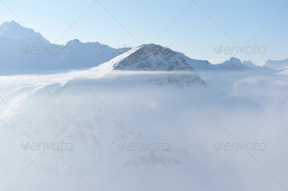 Mountains in clouds with snow in winter - Stock Photo - Images