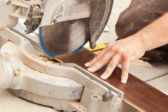 Contractor Using Circular Saw Cutting of New Laminate Flooring Renovation. - Stock Photo - Images