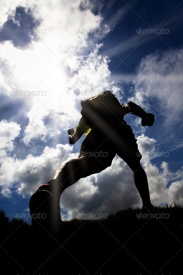 The Silhouette of runner on the grass field with sunlight background - Stock Photo - Images