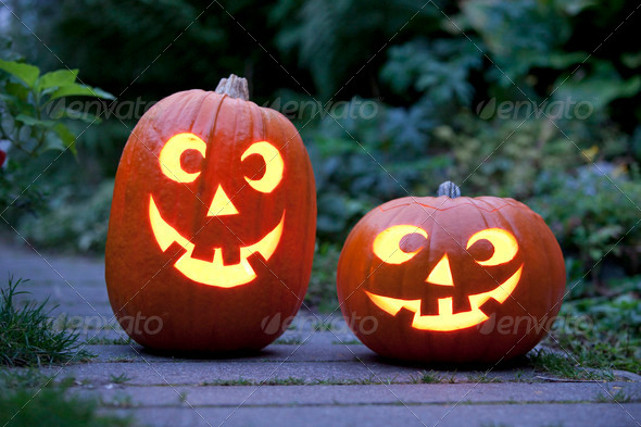 Two Illuminated Halloween pumpkins in the garden - Stock Photo - Images