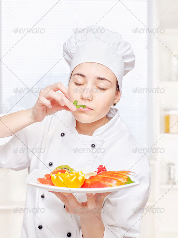 chef smell mint before putting it on a plate of fruit - Stock Photo - Images