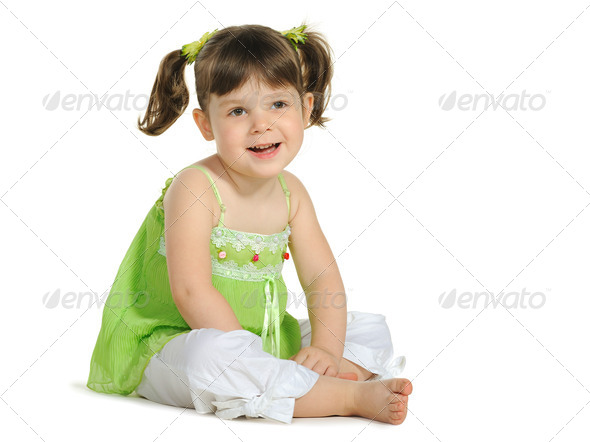 Pretty the little girl sits on the white - Stock Photo - Images