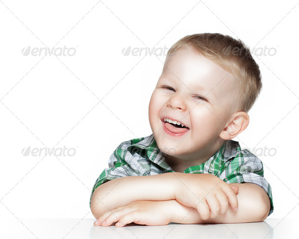Portrait of a cute little boy smiling while sitting at table, is - Stock Photo - Images