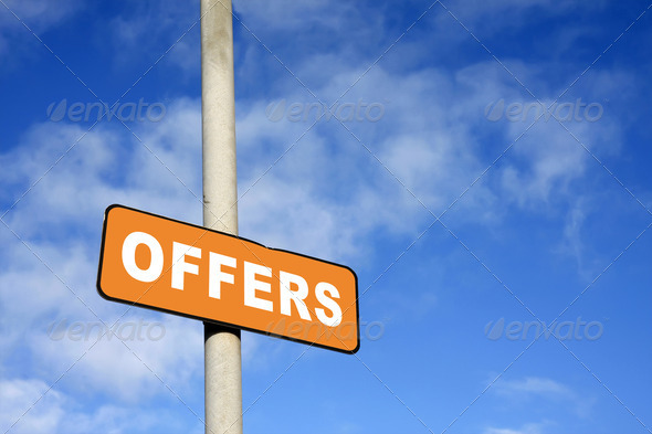 Orange offers sign against a blue sky - Stock Photo - Images