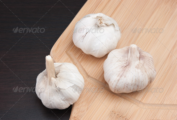 garlic on kitchen cutting board - Stock Photo - Images