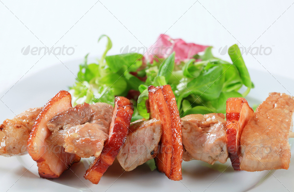 Pork skewer with salad greens - Stock Photo - Images