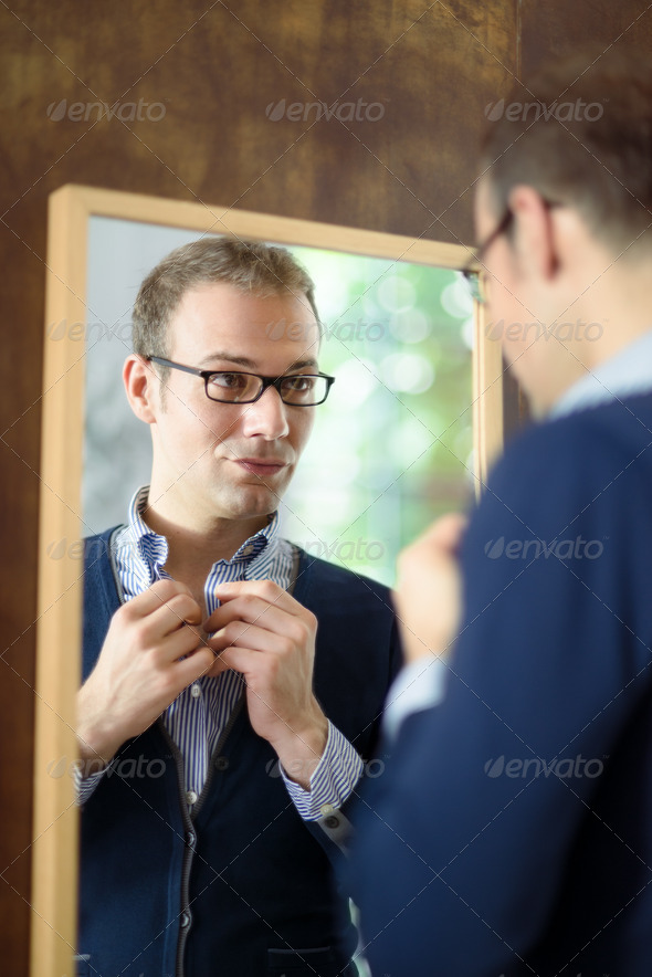 Young man dressing up and looking at mirror - Stock Photo - Images