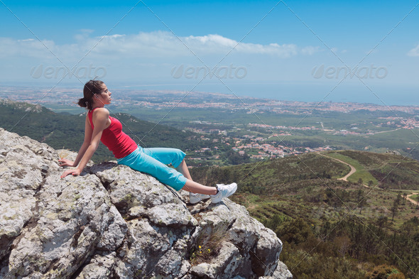 Young athletic girl relaxing on top of rocks - Stock Photo - Images