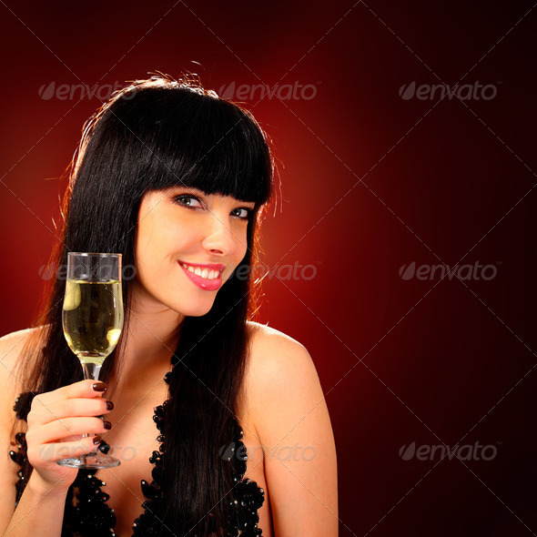 Smiling woman holding a glass of champagne - Stock Photo - Images